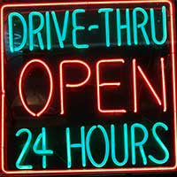 A neon sign reading DRIVE-THRU OPEN 24 HOURS