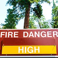 A sign in a forest that reads FIRE DANGER HIGH. Getty Images.