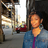 Katanya Raby stands on a Chicago street with the El train in the background. Photo by Sandy Steinbrecher.