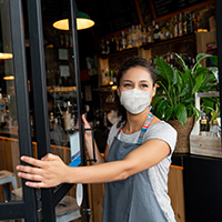 A mask-wearing employee of a small business that's open during the pandemic holds open the door to her shop. Getty Images.