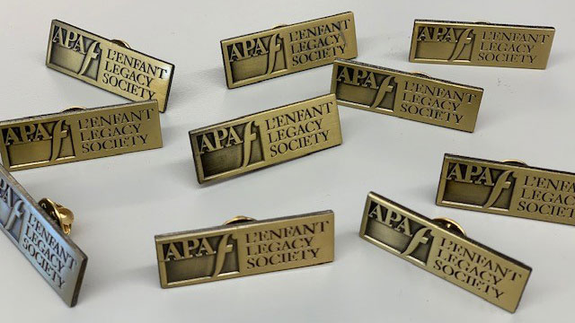 This image features the enamel pin presented to donors of the L'Enfant Legacy Society