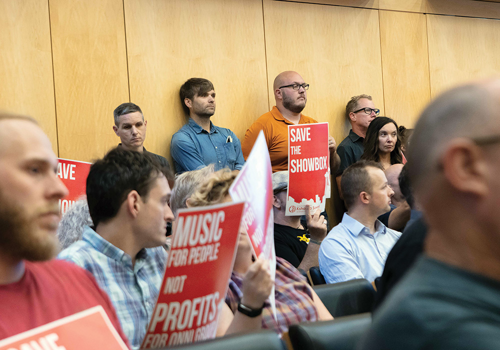 Death Cab for Cutie's Ben Gibbard (top row, in blue shirt) waits in Seattle's city council chambers to comment on the fate of the Showbox. Photo by Lester Black/The Stranger.