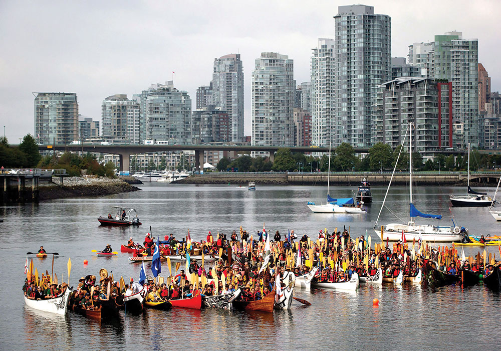 People on First Nations canoes raise their oars during a Reconciliation Week gathering on False Creek in 2013. The plan includes an access point for ceremonial canoe events. Photo by Darryl Dyck, AP Photo/The Canadian Press.