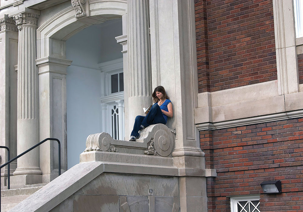 A young woman reading on the grand staircase of Stoddard Johnston Scholar House. Photo courtesy Family Scholar House.