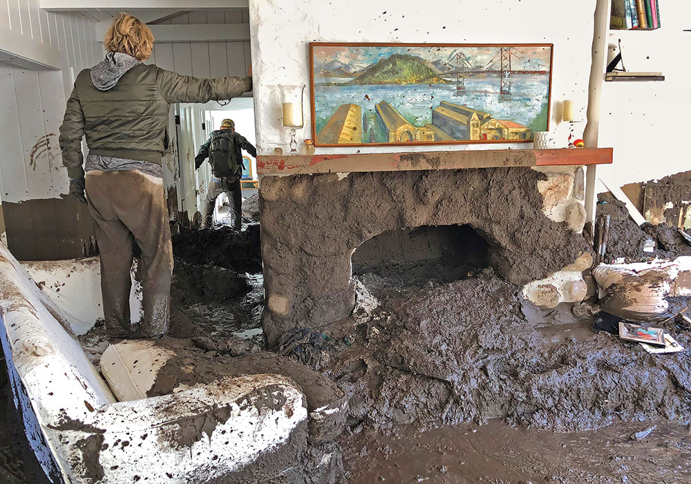 Relatives of Montecito resident Rebecca Riskin search for her belongings in her mud-filled living room. Riskin and her husband were swept away the morning of January 9, 2018, by the debris and boulder-filled San Ysidro Creek. Riskin's body was found later; her husband was rescued by helicopter. Photo by Mike Eliason/Santa Barbara County Fire Department.