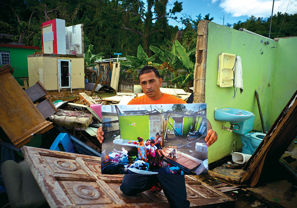 Seven months after his home in Toa Baja was destroyed by Hurricane Maria in October 2017, Arden Dragoni holds a photo of his family taken just after the storm in the same spot. At the time of the 2018 photo, the unemployed construction worker and security guard was separated from his family while his wife and children lived in a FEMA-subsidized apartment and he lived with his father.