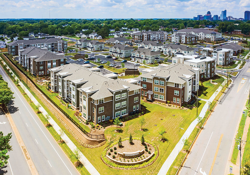 In Raleigh, North Carolina, the developer of the Village at Washington Terrace (foreground, 16 buildings in complex — 14 residential, 1 community center, 1 childcare center) and Booker Park North (top right) had to make up funding shortfalls after federal tax cuts. Photo by Farid Sani Photography.