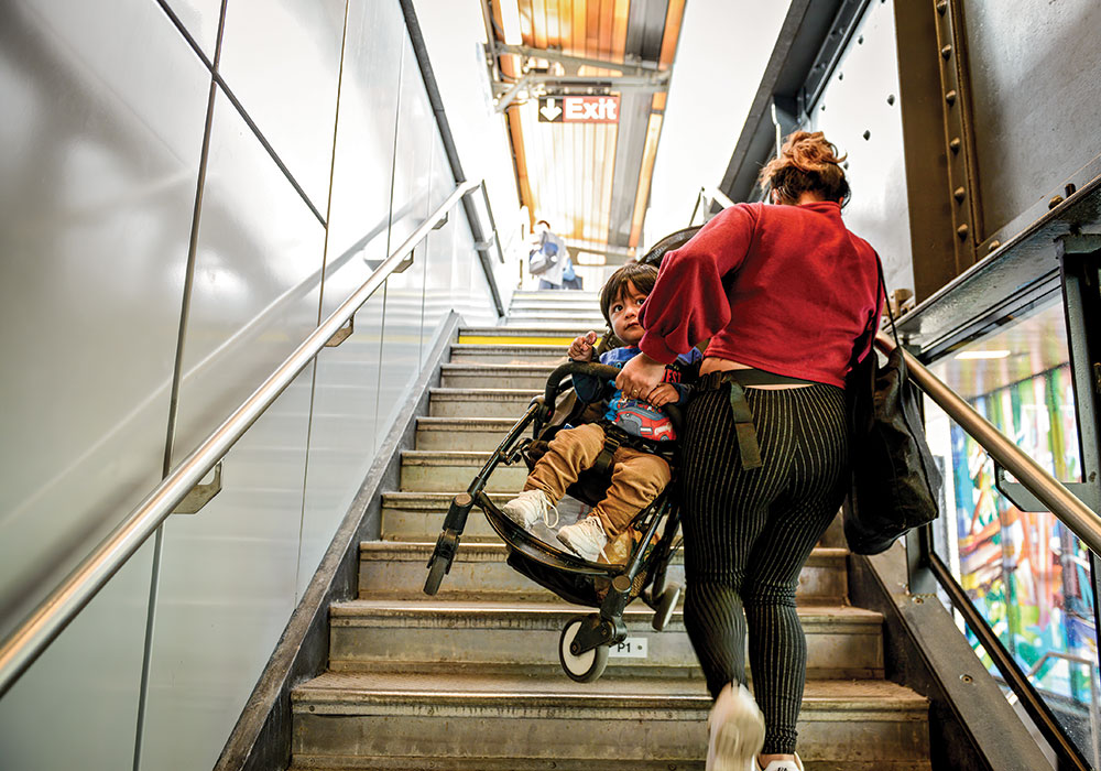 A woman lugs her toddler and stroller up the subway stairs in Queens, New York. Photo by Marian Carrasquero/The New York Times.