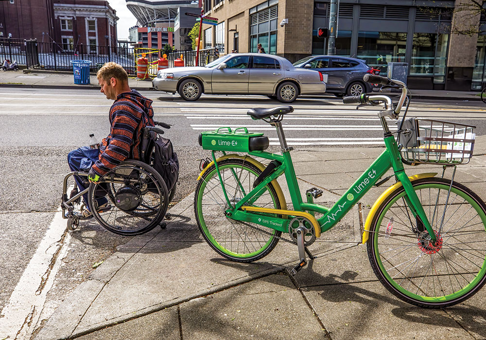 A Seattle wheelchair user maneuvers around a dockless Lime bike partially blocking a curb ramp. Photo by Steve Ringman/The Seattle Times.