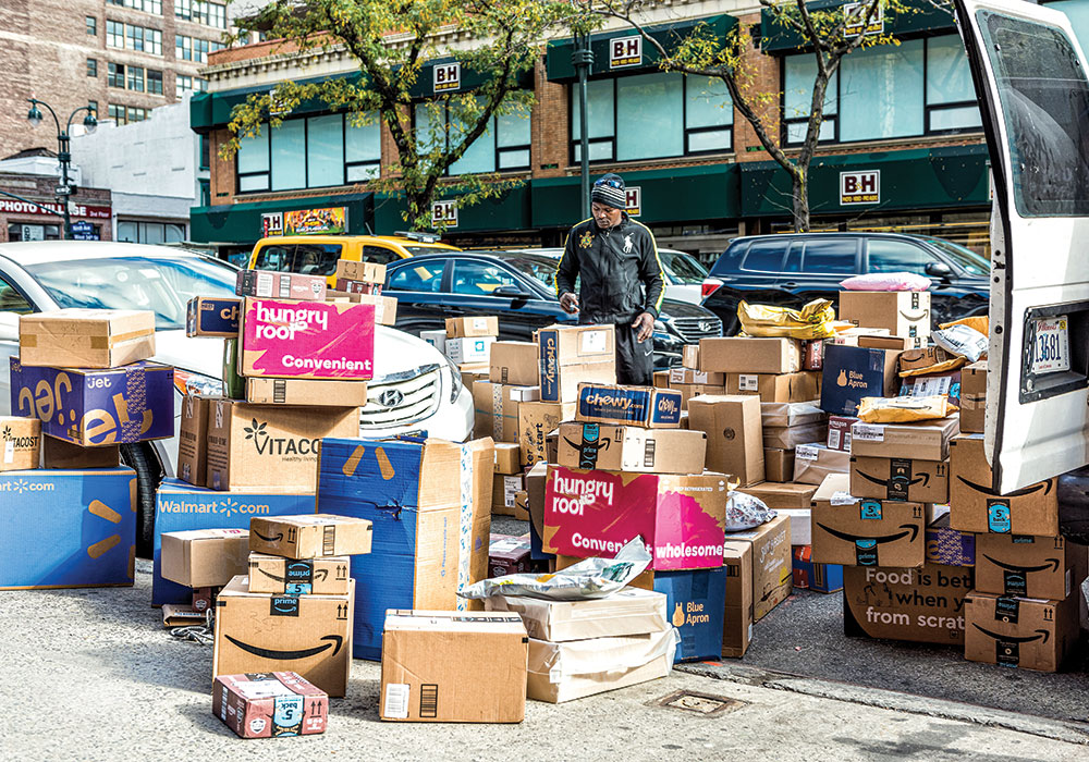 A delivery driver organizes a variety of e-commerce orders — ranging from food kits to pet supplies — on a New York City sidewalk. Photo by Ablokhin/iStock Editorial/ Getty Images Plus.