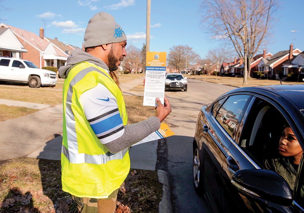 A Detroit Water & Sewerage Department employee gives information to residents about restoring their water service. The city suspended shutoffs as a public health and safety measure during the early days of the COVID-19 outbreak. Photo by Rebecca Cook/Reuters.