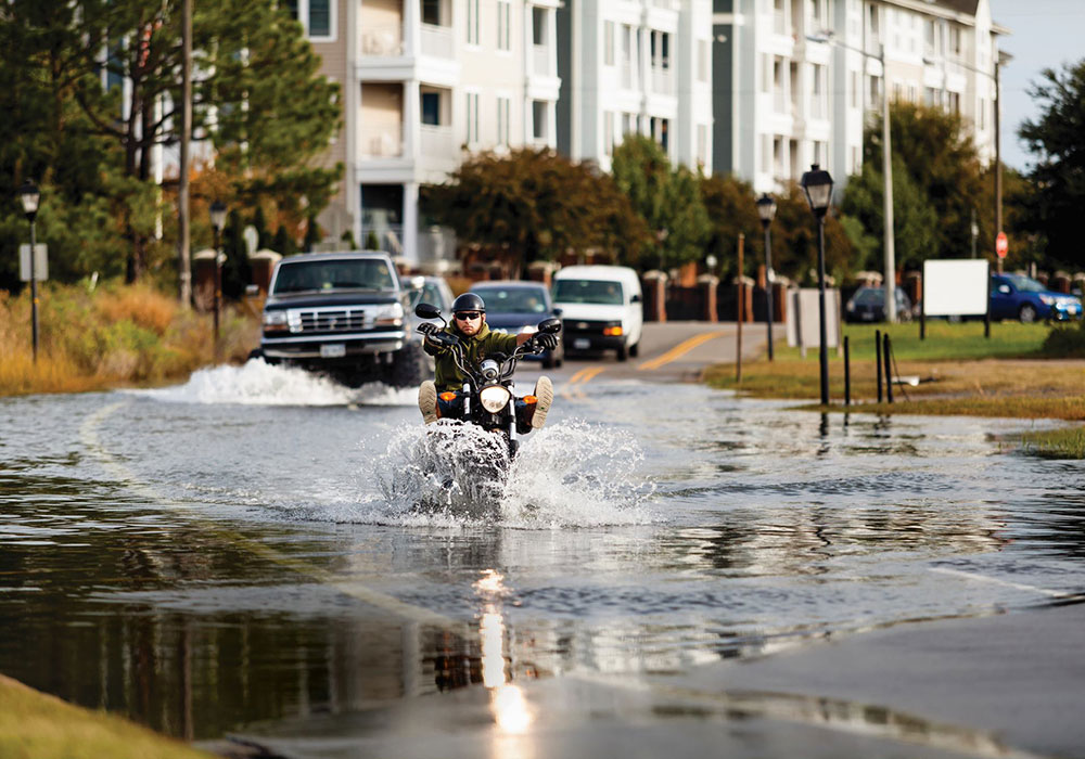 Motorists drive through a flooded street in Norfolk, Virginia, during a period of high-tide flooding. Climate change is causing these episodes to occur more frequently. Photo by Will Parson/Chesapeake Bay Program.
