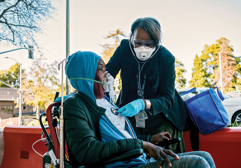 """A respiratory therapist cares for a patient in Oakland, California, where a COVID-19 Racial Disparities Task Force was created in May. Race is a huge factor in virus fatality rates due to """"long-standing systemic health and social inequities,"""" the CDC says. Photo by Alexandra Hootnick/The New York Times."""