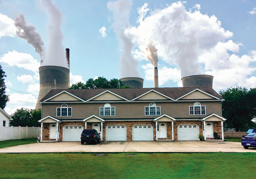 The John Amos Power Plant looms over nearby apartments in Winfield, West Virginia. During the onset of the pandemic in the U.S., the Trump administration significantly relaxed regulations that limit toxic metal output from coal-fired plants. John Raby/AP Photo.