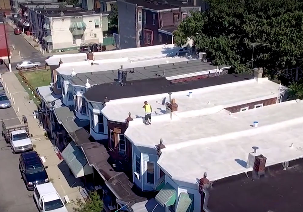 Members of the Roof Coatings Manufacturers Association cover roofs with rubberized white paint in Philadelphia to help keep buildings cooler. The city's Beat the Heat program identified cool roofs as one tool against the heat island effect. Photo courtesy Energy Coordinating Agency Philadelphia.