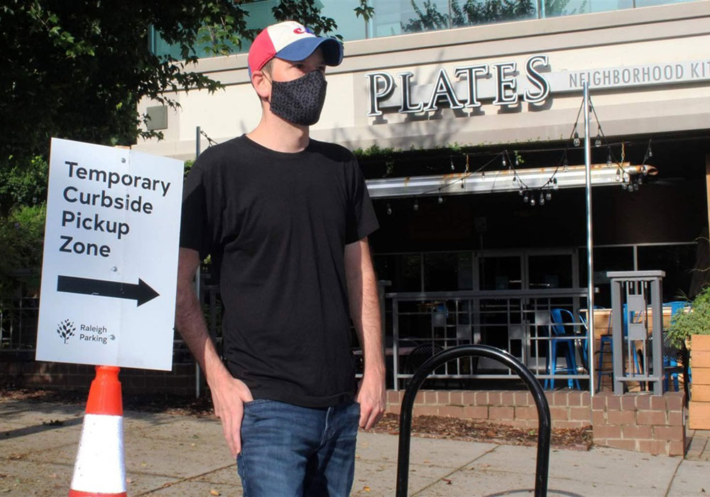 In downtown Raleigh, North Carolina, Justin Gallus stands outside his Plates Neighborhood Kitchen restaurant and one of the city-created curbside pickup zones that's helped the business stay afloat during the pandemic. Photo courtesy Pew Charitable Trusts.