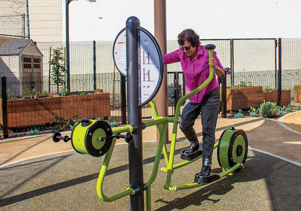 A UCLA professor tries out the equipment at an all-ages CLT park in Los Angeles she designed with residents. Photo by Mary Braswell/UCLA Luskin School of Public Affairs.