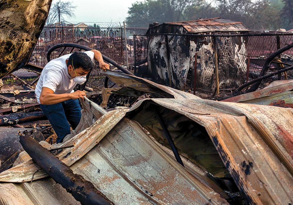 Moses Reyes searches the wreckage of his mobile home in Talent, Oregon, following the Almeda Fire. More than 2,300 homes were destroyed in the blaze. Photo by Alisha Jucevic/The New York Times.