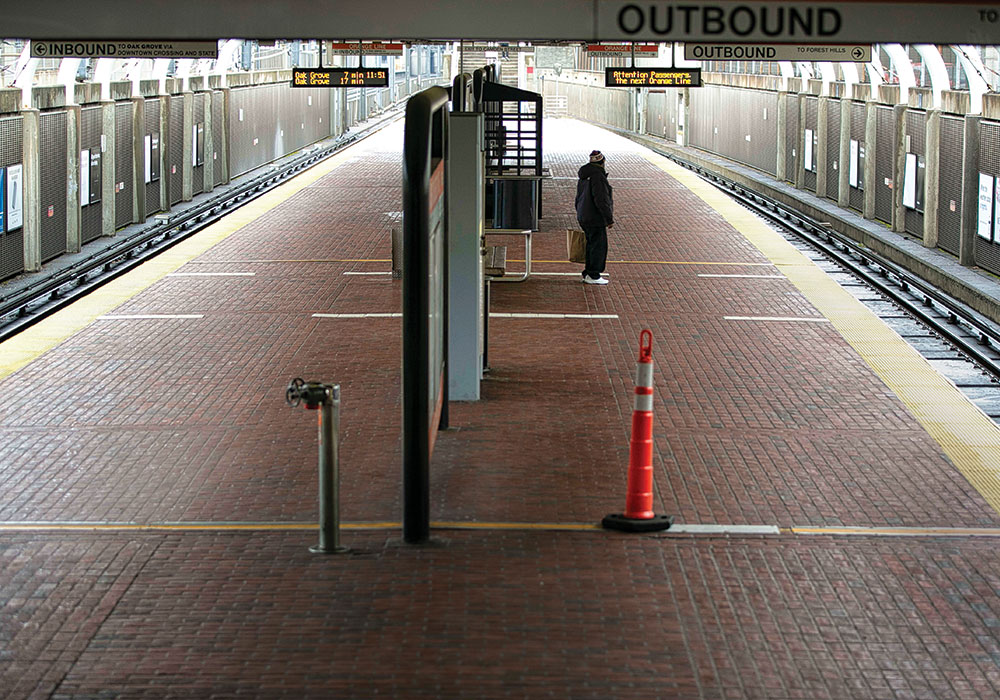 A lone traveler waits at a Boston subway station in March, when state and local governments began issuing emergency closures and mandates due to COVID-19. Photo by Katherine Taylor/The New York Times.