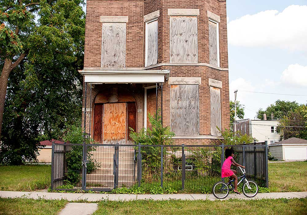 Artist Tonika Lewis Johnson cataolgues the individual, societal, and economic impacts of segregation on her hometown of Chicago, one of the most racially segregated cities in the country. Here, a young girl rides her bike past a boarded up building on the city's South Side. Photo by Tonika Lewis Johnson.