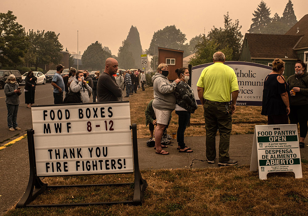 The Holiday Farm Fire forced these Lane County, Oregon, residents from their homes in September. Here, they line up for food and financial aid at a church in nearby Springfield. Photo by Bryan Denton/The New York Times.