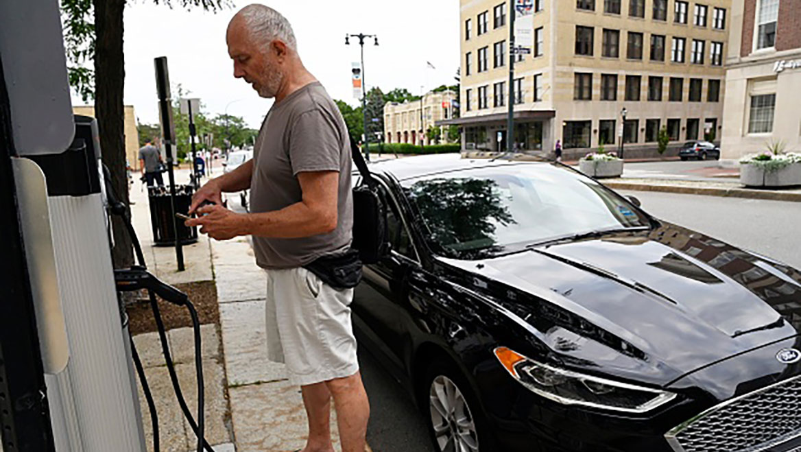 Laurence Kelly finishes a transaction at the EV charging station in front of Portland, Maine's city hall. By charging a fee for electricity, the city will now break even on its charging stations. Photo by Shawn Patrick Ouellette/Portland Press Herald/Getty Images.