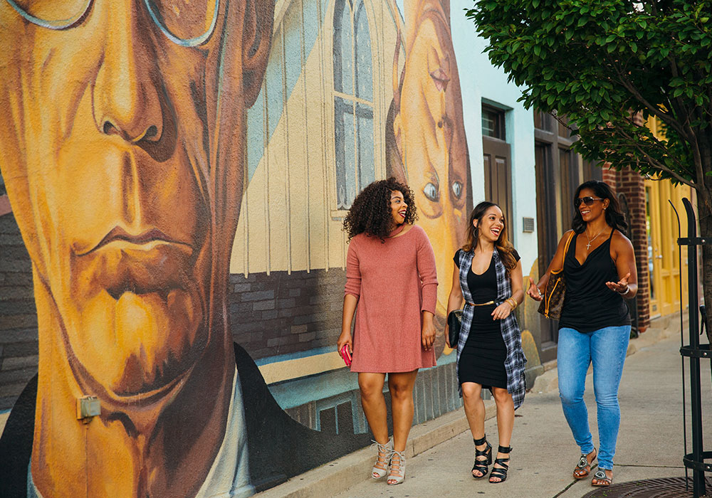 Young women in front of the American Gothic mural in Short North Arts District. Photo by Levi Ely.