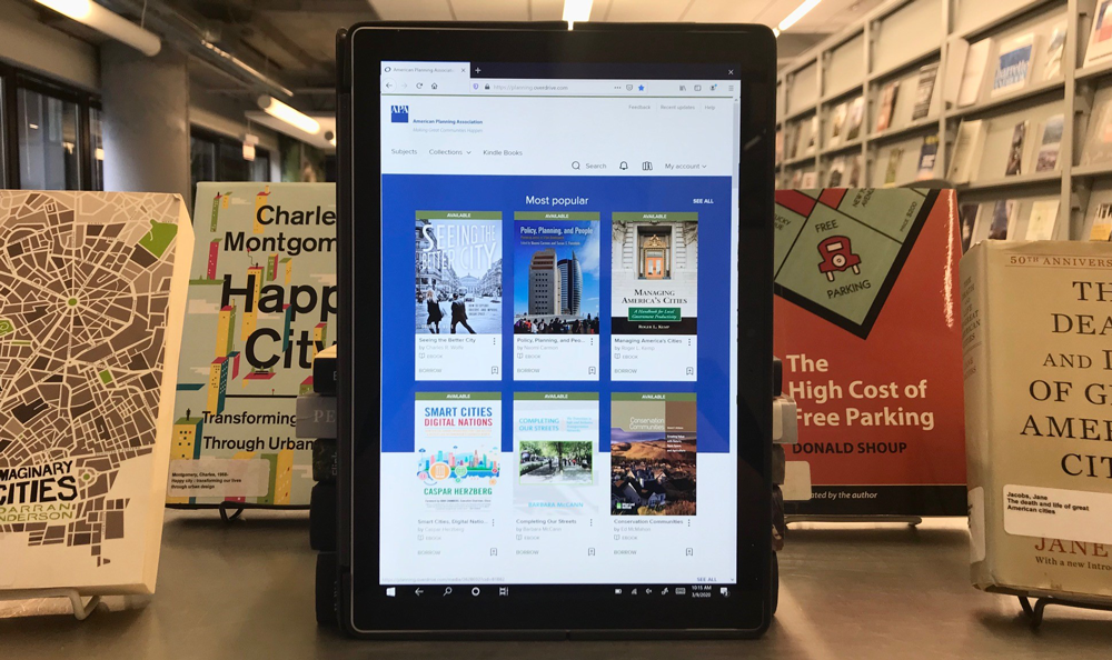 A tablet displays the homepage for the E-book Collection while sitting in the APA Library.
