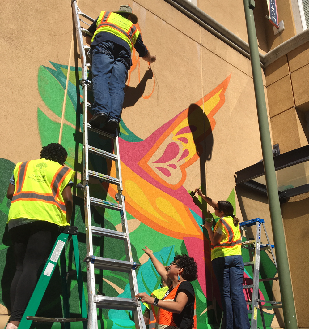 Artist Faviana Rodriguez directs volunteers in the creation of a community mural as part of the Divisions Day of Service. Photo by Maggie Kraus.
