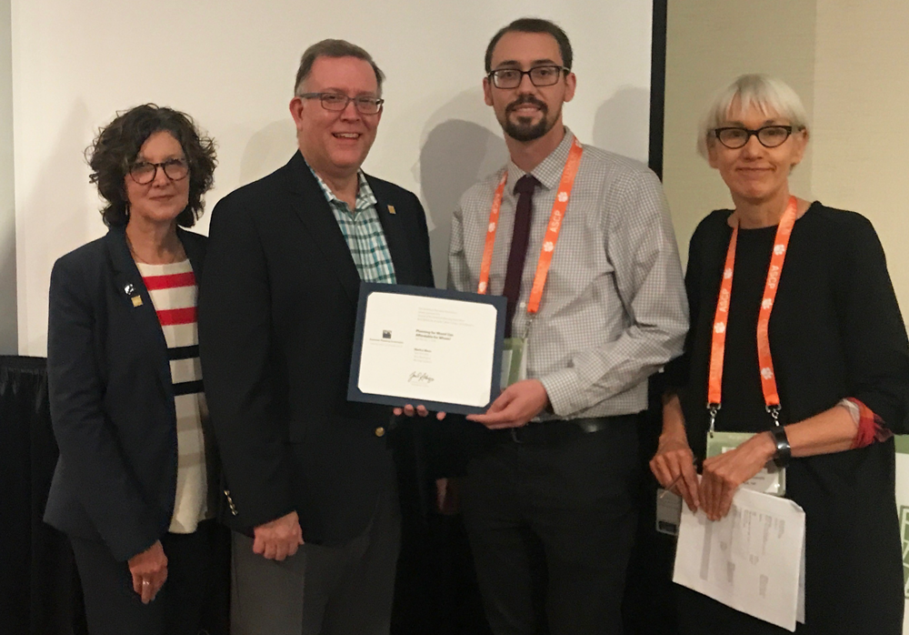 AICP President Deborah Lawlor, FAICP; APA President Kurt Christiansen, FAICP; and Journal of the American Planning Association Editor Ann Forsyth, PhD, present the 2019 JAPA Best Article by an Early Career Scholar Award to one of the article's co-authors, Nick Revington of the University of Waterloo, Canada (holding certificate), who accepted on behalf of award recipient Markus Moos.