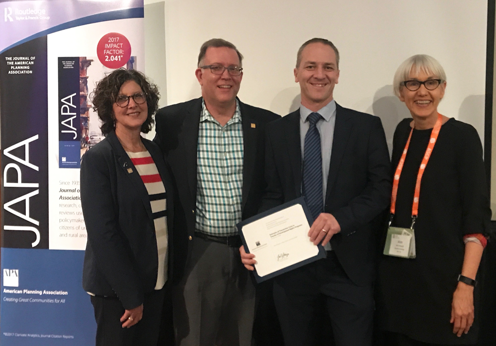 AICP President Deborah Lawlor, FAICP; APA President Kurt Christiansen, FAICP; and Journal of the American Planning Association Editor Ann Forsyth, PhD, present the 2019 JAPA Best Article Award to one of the three authors, Associate Professor Eoin O'Neill of University College Dublin (holding certificate). The presentation was made at the 2019 ACSP conference in Greenville, South Carolina.