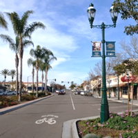 """Class III Bike Route – Provides shared use of traffic lanes with cyclists and motor vehicles, identified by signage and/or street markings such as """"sharrows."""" Bike routes are best suited for low-speed, low-volume roadways. Bike routes provide network continuity or designate preferred routes through corridors with high demand. Photo of Third Avenue in Chula Vista, California."""