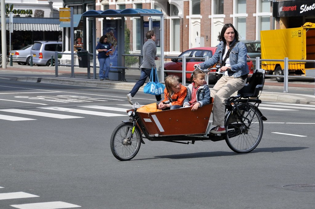 A woman transports children on a cargo bike in the Netherlands. Photo by Ballenbak from Wikimedia (CC BY 2.0).