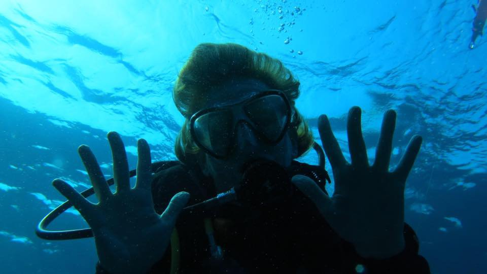 Scuba diver poses for a photo under water with a regulator in mouth